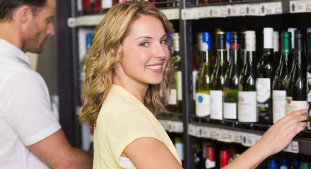 Portrait of smiling pretty woman buying a wine bottle