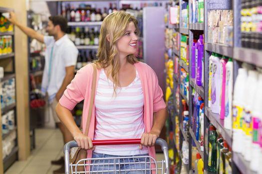 Smiling blonde woman looking at shelf