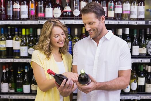 Smiling casual couple looking at wine bottle