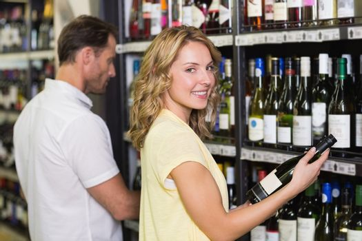 Portrait of a smiling pretty woman looking at wine bottle