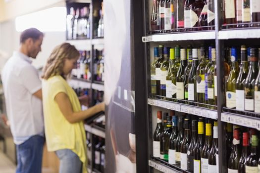 Pretty woman and handsome buying a wine bottle