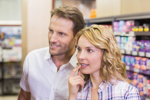 Smiling casual couple looking at shelf