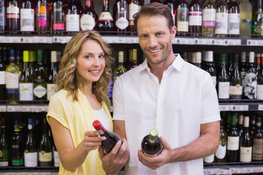 Portrait of a smiling casual couple looking at wine bottle