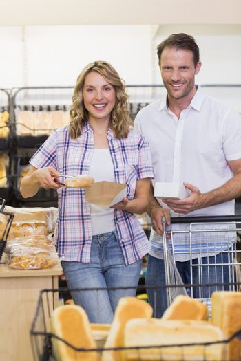 Portrait of a smiling casual couple taking a bread