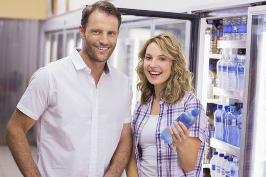 Portrait of a smiling casual couple having a water bottle