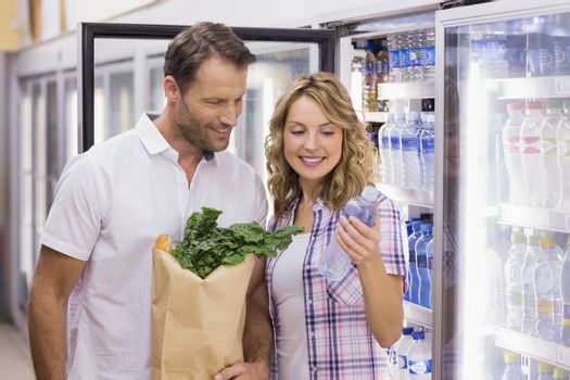 Smiling casual couple looking at water bottle