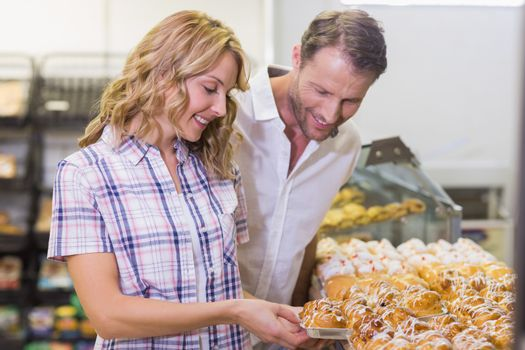 Smiling casual couple taking a pastry