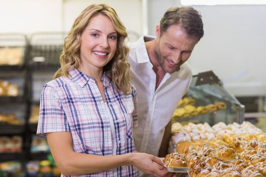 Portrait of a smiling blonde woman taking a pastry