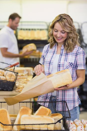 Smiling blonde woman taking a bread in her paper bag