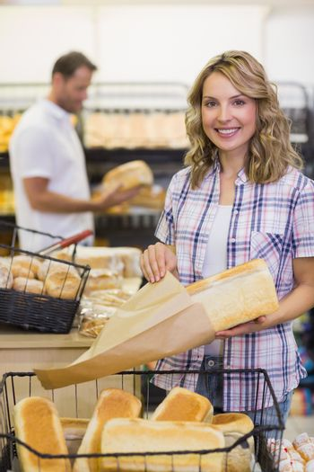 Portrait of a smiling blonde woman taking a bread on her paper bag