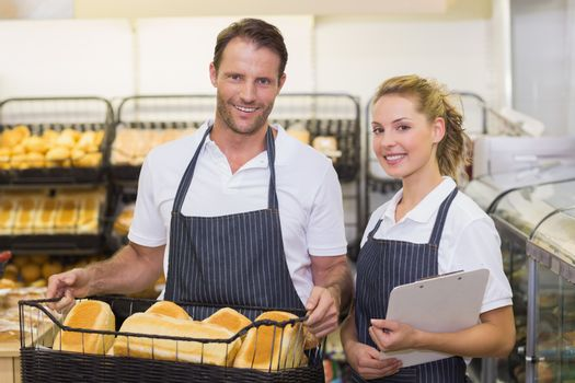 Portrait of a smiling bakers hoding a basket with bread and notepad