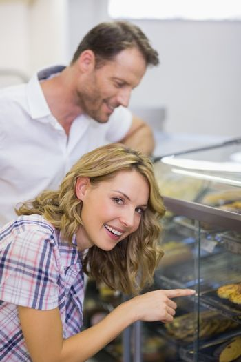 Portrait of a smiling blonde woman looking at pastry