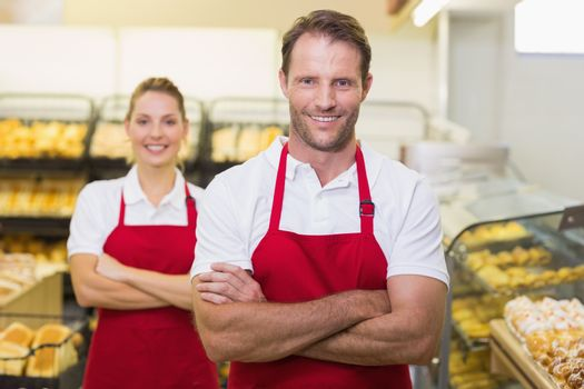 Portrait of smiling two bakers with arms crossed