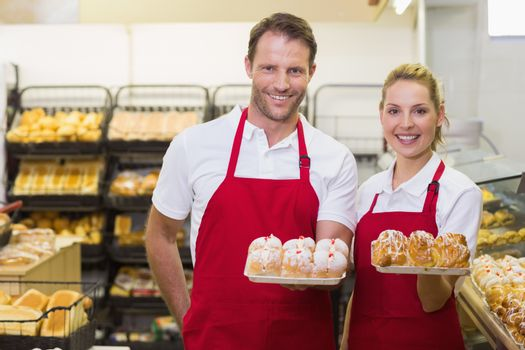 Portrait of smiling bakers having a pastry