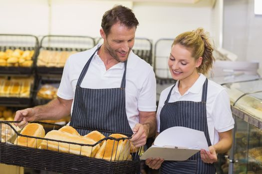 Smiling bakers looking at notepad and holding a basket with bread