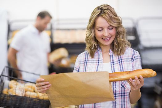 Smiling blonde woman looking at a bread