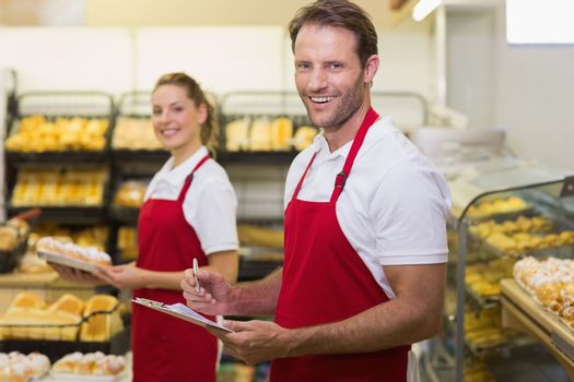Portrait of a two smiling bakers looking at camera