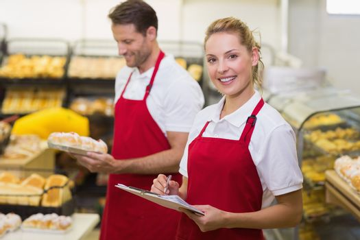 Portrait of a smiling baker with her colleague