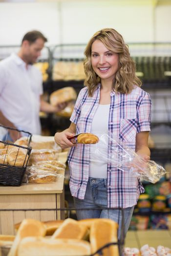 Portrait of a smiling blonde woman taking a bread