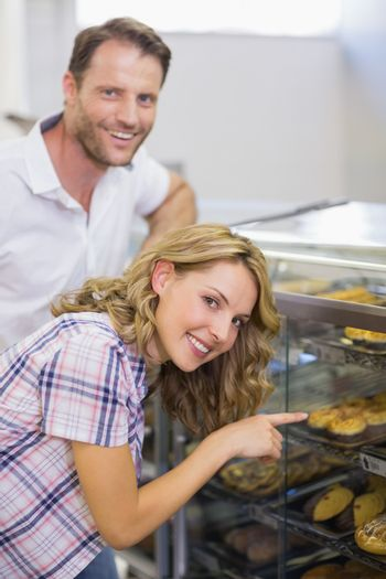 Portrait of a smiling blonde woman showing a pastry