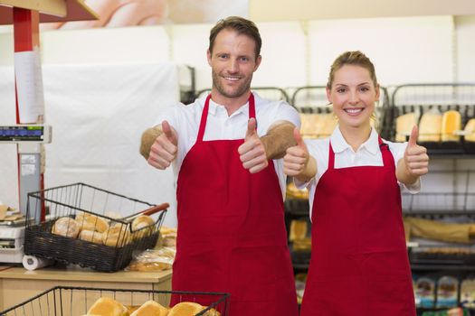 Portrait of smiling bakers with thumb up