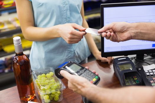 Woman at cash register paying with credit card