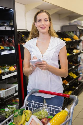 Woman writing in her notepad in aisle