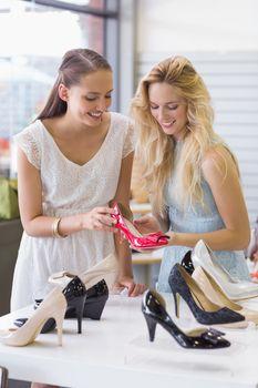 Two happy women looking at heel shoe