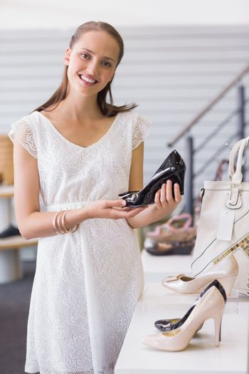 Pretty brunette smiling at camera and showing a heel shoe