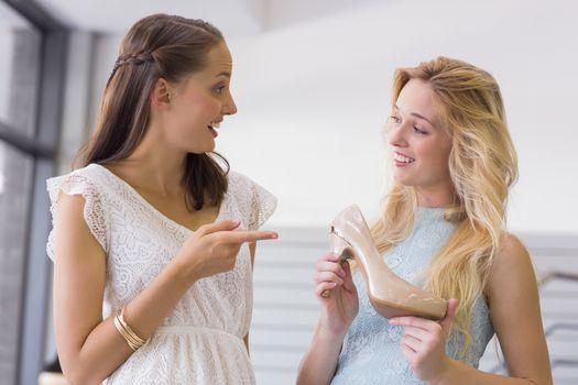 Happy women showing a heel shoe