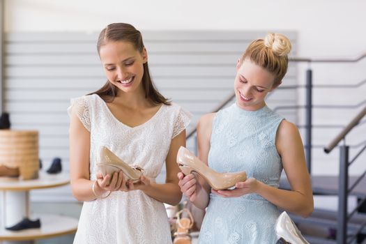 Two happy women holding heel shoes