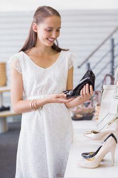 Pretty brunette looking at a heel shoe