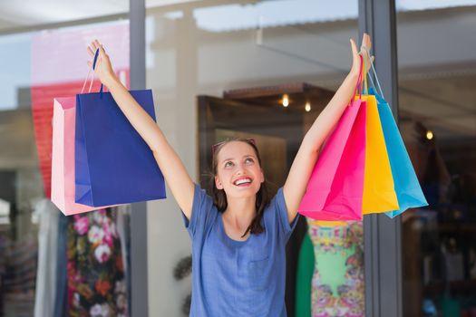 Energetic woman handing shopping bags