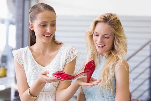 Happy women looking at a heel shoe