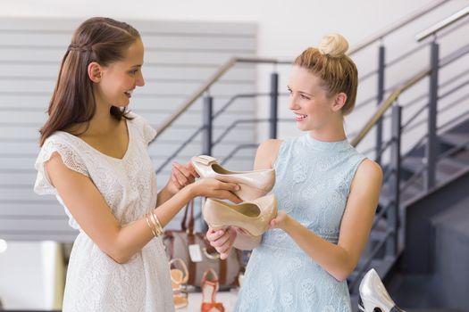 Happy women looking at heel shoes