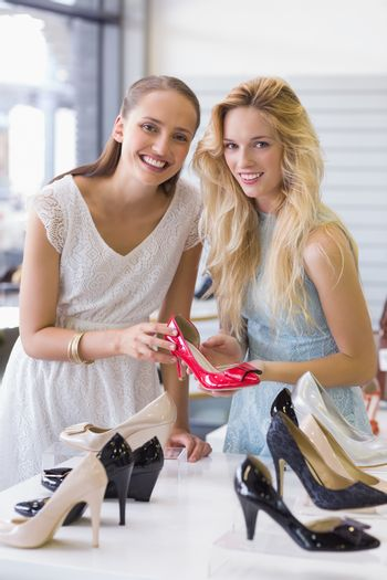 Happy women smiling at camera and showing a heel shoe