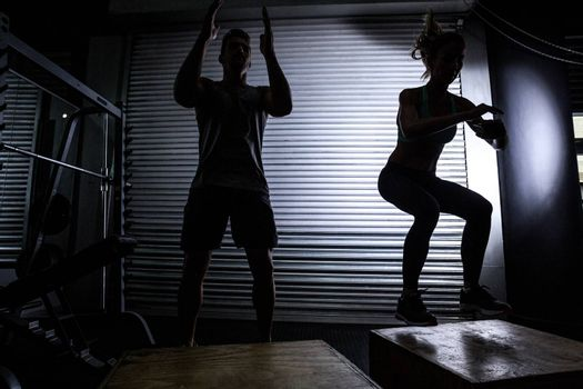 Muscular couple doing jumping squats on a wooden box