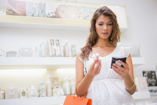 Woman looking at herself in handheld mirror