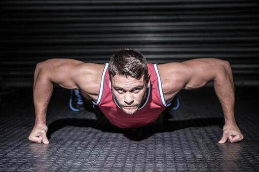 Portrait of muscular man doing push-ups