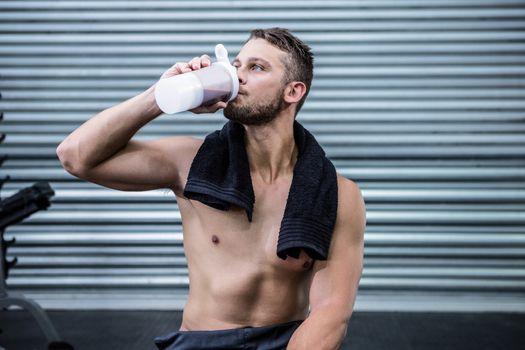 Muscular man drinking protein cocktail