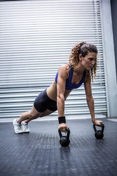 Muscular woman doing push-ups with kettlebells