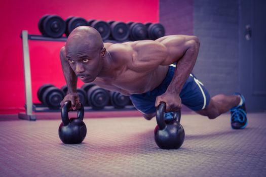 Muscular man doing push-ups with kettlebells