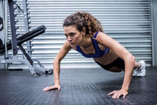Muscular woman doing push-ups