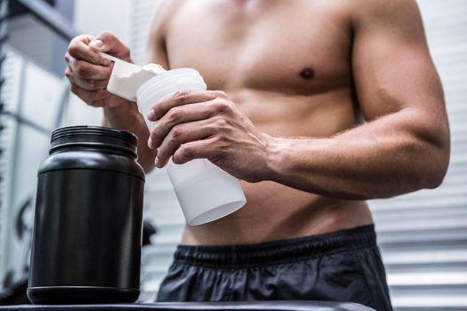 Muscular man making protein cocktail