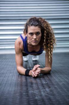 Portrait of muscular woman doing push-ups
