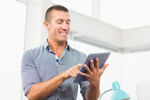 Smiling businessman scrolling on his tablet