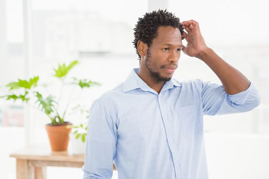 Young thinking businessman scratching his head