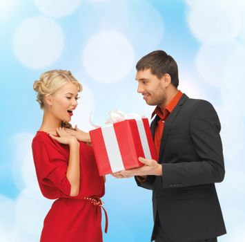 christmas, holidays, valentine's day, celebration and people concept - smiling man and woman with present over blue lights background
