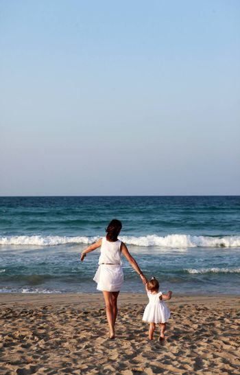 Happy mother holding her daughter on the beach