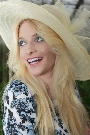 Close up Stylish Pretty Blond Woman Wearing Elegant Straw Hat and Looking Into the Distance with Happy Facial Expression.
